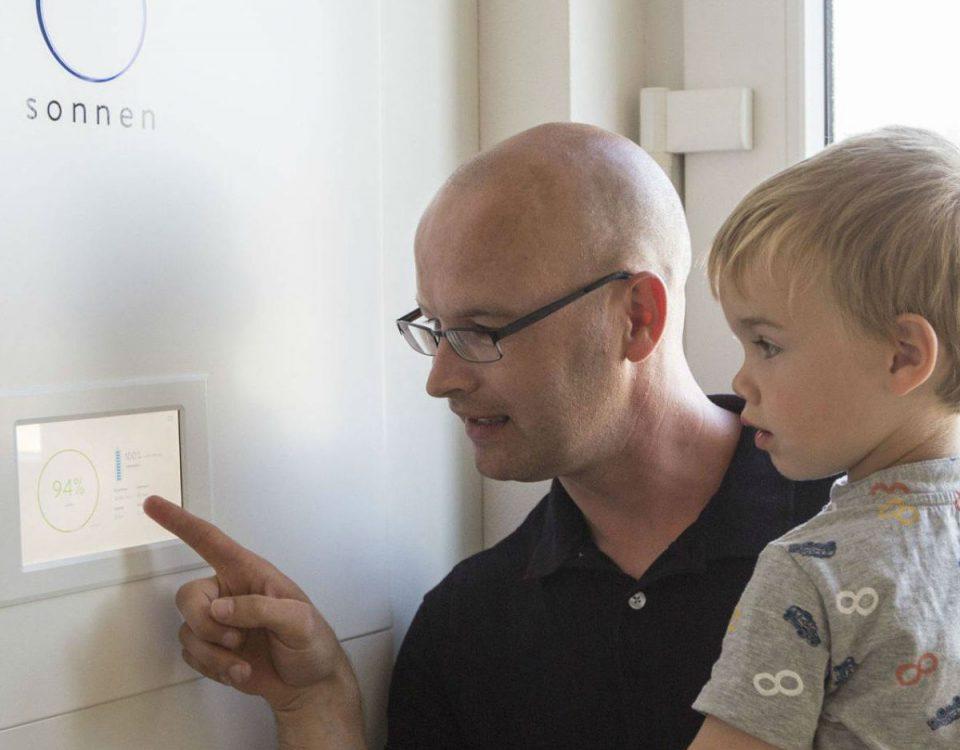 Un padre revisa el consumo en una batería recargable de energía solar instalada en su casa en la localidad alemana de Schwedt, junto a la frontera polaca. Fuente: El País